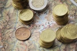 Euromünzen über einer Landkarte von Tirol